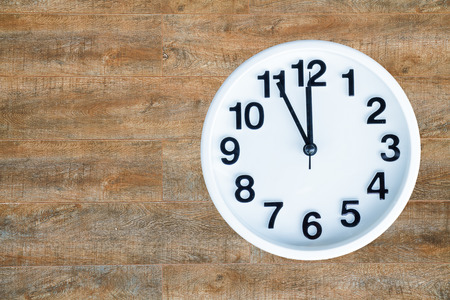 pm: Clock show 5 minute to 12 am or pm on wood background with copy space. clipping path in picture.