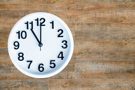 Clock show 11 am or pm on wood background with copy space.