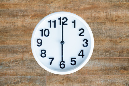 pm: Clock show 6 am or pm on wood background with copy space.