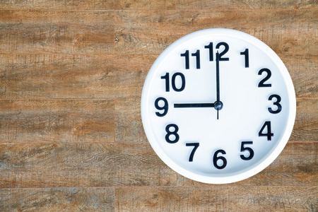 pm: Clock show 9 am or pm on wood background with copy space.