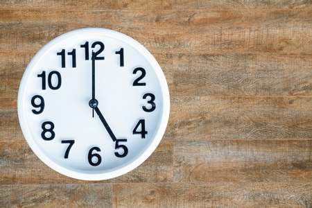 Clock show 5 am or pm on wood background with copy space.