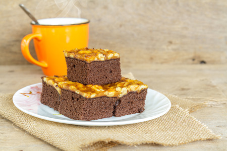 plato del buen comer: Toffee cake garnish with cashew and hot coffee on wooden table.