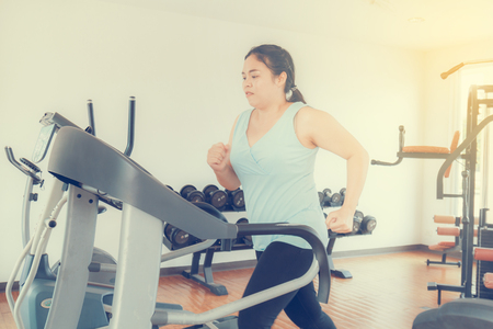 Asia fat woman run electric treadmill in the gym for strength, weight loss.