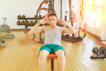 situp: Asia man middle aged sit up in the gym for strength, weight loss.