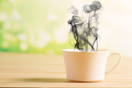 suggests: Coffee cup and black smoke background green nature bokeh. Concept Suggests that coffee may sometimes be toxic. Stock Photo