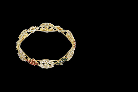 Gold bracelets with gem and diamonds isolate on black background.