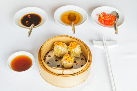 Dim sum food Steamed pork dumpling in bamboo basket at restaurant with soy sauce, sweet sauce, chili sauce and chopsticks.