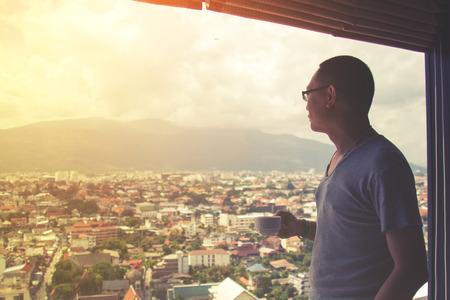 Uomo asiatico azienda tazza di caffè in ufficio che osserva fuori finestra. sfondo paesaggio urbano. messa a fuoco selettiva e filtro bagliore morbido. Archivio Fotografico