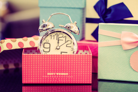 Alarm clock and gift box with copy space. Vintage or Retro tone. Stock Photo