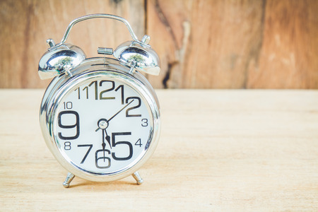 Clock show 5 am or pm and 30 minute on wood background with copy space.