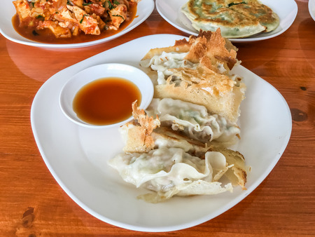 Dim sum : Gyoza, it made wrappers and meat in white plate on wood table.