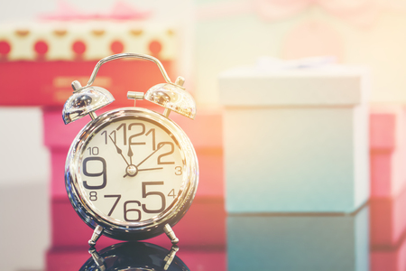Alarm clock and gift box with copy space. Vintage or Retro tone. Selective focus and soft flare sunlight. Stock Photo