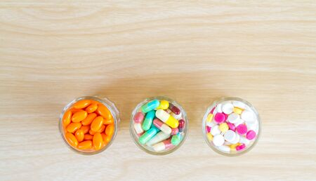 Medicine is pill and capsule in glass with copy space on wood table. top view. Stock Photo