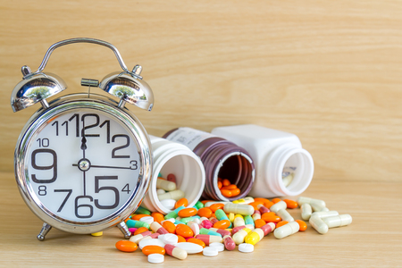 Medicine is pill and capsule clock show 12 am or pm with copy space on wood table.