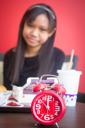 pm: Alarm clock show 12 hour time for lunch background girl eat fast food. Stock Photo