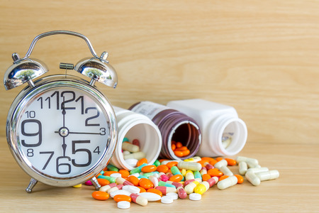 prophylactic: Medicine is pill and capsule clock show 6 am or pm with copy space on wood table. Stock Photo