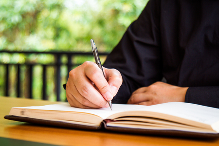 autograph: Businessman write a book on workplace with copy space. Stock Photo