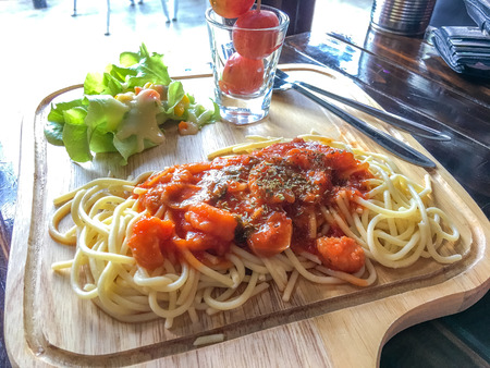 Spaghetti tomato sauce and shrimp with butter head on wood plate on wooden table. Stock Photo