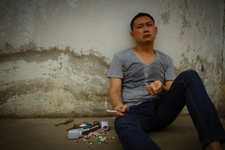 Asia man smoking cigarette is sad and pain by drug addiction problem. World no tobacco day, 31 may. Stock Photo