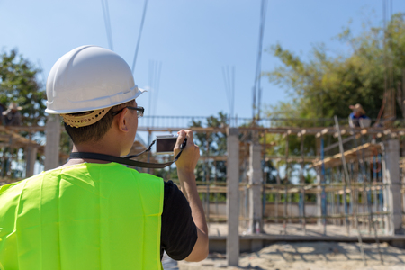 Engineers wear a helmet and holding construction plan and camera monitoring the construction area.