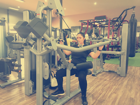 Asia fat girl training arm equipment in the gym for strength, weight loss.