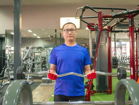 Asian man middle aged is trained with barbell in the gym for strength and weight loss.