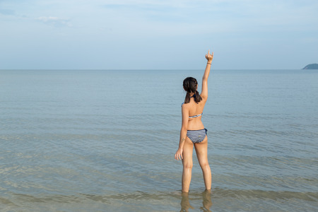 Asia teenage girls wearing bikini and hand gesture language translates to love at the beach with copy space.