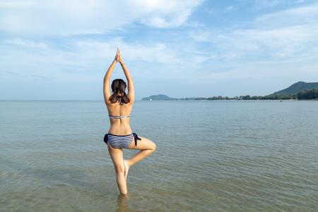 Asia teenage girls wearing bikini at the beach background blue sky with copy space.