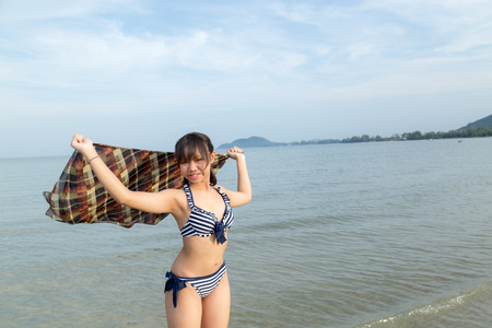 Asia teenage girls wearing bikini at the beach with copy space.