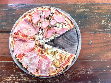 Pizza with seafood, salami and sausage on wooden table in restaurant. top view or flat lay. 版權商用圖片