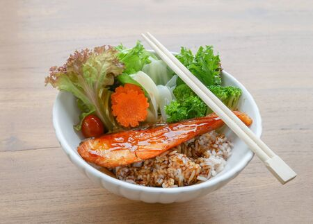 Japan food is Salmon grill don with rice, vegetable and carrot topped with teriyaki sauce in bowl.