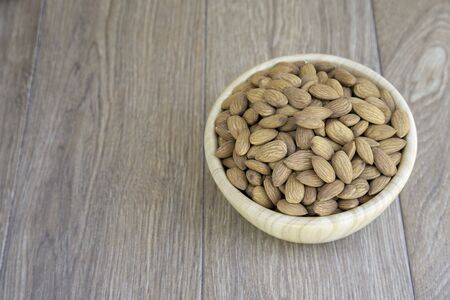 Almond nut in wooden bowl on wood background with copy space. Stock Photo