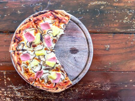 Pizza with bacon mushroom and pineapple on wooden table in restaurant. top view or flat lay.