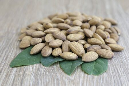 Almond nut on green leaf on wood background with copy space.