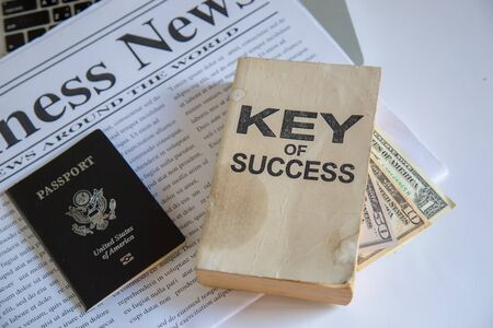 Book key of success on table and news, passport and laptop. top view or flat lay. Stock Photo