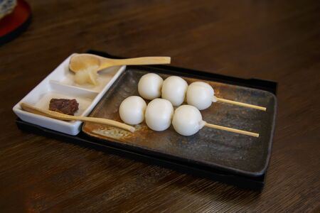 Dango is Sweet dessert make rice flour with skewer on wooden table in restaurant. Japanese traditional style.