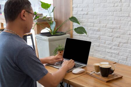 Asia middle age freelance working on laptop at restaurant or cafe. The blank screen with copy space for your text or advertising content. Clipping path on picture.