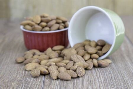 Almond nut and ceramic cup on wood background with copy space.