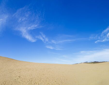 Tottori sand dune in Tottori prefecture is famous for Japan. It is sand dune seaside background is blue sky with copy space. Stock Photo