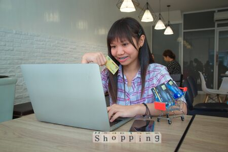 Asian ethnicity teenager woman holding credit card for online shopping online from the laptop in a cafe. On a wooden table, there is letter made of wooden blocks written as Shopping. Selective focus.