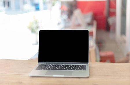 Computer laptop on wood table in cafe or restaurant. The blank screen with copy space for your text or advertising content. Selective focus and clipping path on picture.