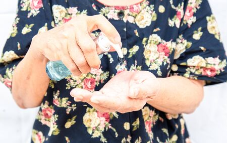 Asian elderly woman Asia ethnic holding an alcohol gel for hand washing to prevent viruses or coronavirus or covid-19 with white background. Stock fotó