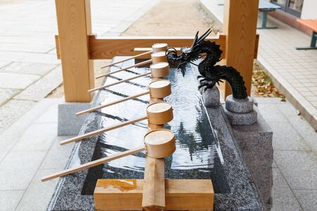 Water ladle made of wood and pond in front of Shinto shrine for washing hand and gargle mouth before entering the shrine. Stock fotó