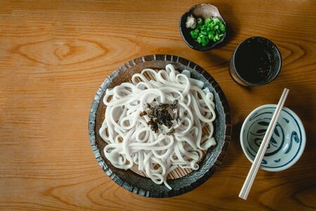 Cold udon in a black ceramic plate with wasabi, green onion and wooden chopsticks on the wood table. top view. Stock fotó