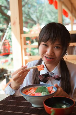 A girl teenage woman ethnic Asian is eating a salmon don is raw salmon with rice by chopsticks in a Japanese restaurant. Looking at the camera and smiling.