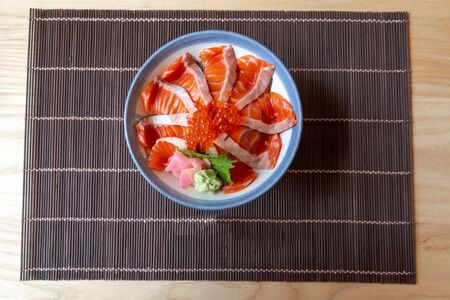 Salmon Don Consisting of sliced salmon on top of Japanese rice and topped with fish spawn Served with wasabi and pickled ginger In a white-blue bowl on a wooden table. top view.