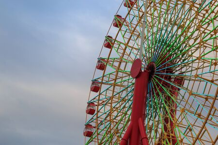 Mosaic ferris wheel at Harborland port of Kobe, Japan. Taken from the bottom corner backdrop the sky and cloud.