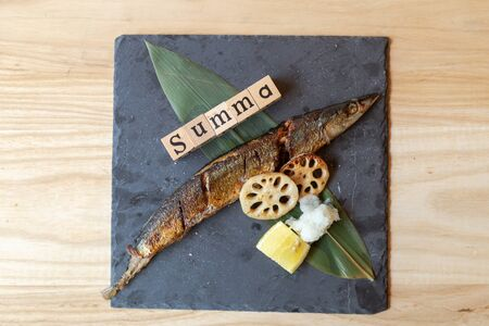 Sanma Shioyaki is Grilled Summa fish with salt on a black plate, served with lemon, grated radish and grilled lotus root On a wooden table in a Japanese restaurant. top view.