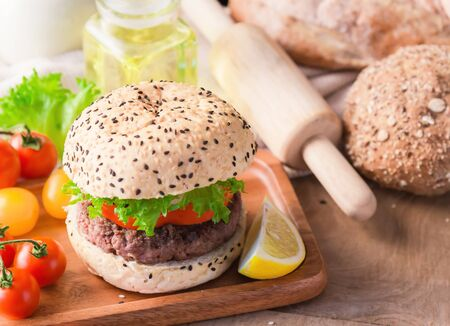 Hamburger homemade on wood table with copy space. Standard-Bild