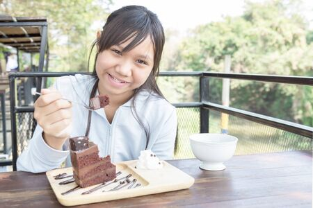 Asia teenage girl eating cake chocolate in restaurant or cafe.